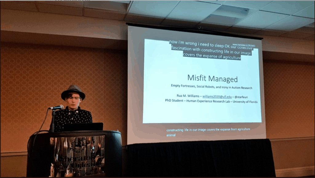 "Image of Rua Williams wearing a fedora, glasses, bow tie, and polka-dot shirt presenting in front of a screen that shows the first slide of the ""Misfit Managed"" presentation. Captions can be seen on both the top and bottom of the screen. The top captions are from Microsoft Translator and the bottom ones are from PowerPoint's built in captioning system."